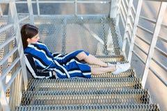 Femme s'asseyant sur des escaliers en métal Photos stock