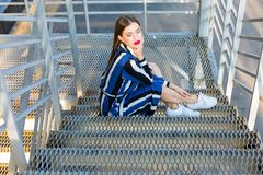 Femme s'asseyant sur des escaliers en métal Photo libre de droits