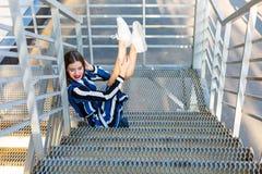 Femme s'asseyant sur des escaliers en métal Image libre de droits