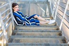 Femme s'asseyant sur des escaliers en métal Photo stock