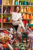 Femme s'asseyant sur des pointeaux de tricotage de fixation de selles image stock