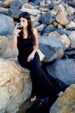 Femme s'asseyant sur des roches appréciant le vin rouge italien devant partie sur des roches Photo libre de droits