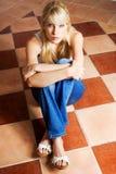 Femme s'asseyant sur l'étage Image libre de droits