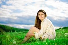 Femme s'asseyant sur l'herbe Photographie stock libre de droits