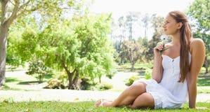 Femme s'asseyant sur l'herbe avec une fleur Photographie stock
