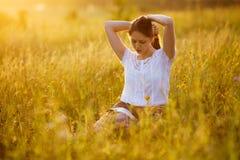 Femme s'asseyant sur l'herbe lisant un livre photographie stock