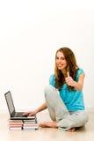 Femme s'asseyant sur l'étage utilisant l'ordinateur portatif Image libre de droits