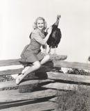 Femme s'asseyant sur la barrière choyant sa dinde photo stock
