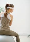 Femme s'asseyant sur la bille de forme physique de nouveau à l'appareil-photo Photographie stock libre de droits