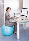 Femme s'asseyant sur la boule de pilates utilisant l'ordinateur Photo libre de droits