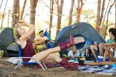 Femme s'asseyant sur la chaise avec des amis au terrain de camping Photos libres de droits