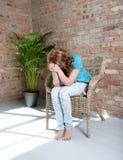 Femme s'asseyant sur la chaise dans la dépression Photographie stock libre de droits