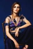 Femme s'asseyant sur la chaise dans le soutien-gorge et le pantalon bleus Photos stock