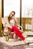 Femme s'asseyant sur la chaise parlant au téléphone à la maison Image stock