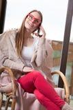 Femme s'asseyant sur la chaise parlant au téléphone à la maison Image libre de droits