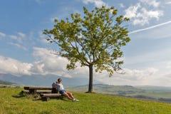 Femme s'asseyant sur la colline d'été près de Liptovsky Trnovec, Slovaquie images libres de droits