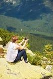 Femme s'asseyant sur la montagne Photo libre de droits