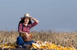 Femme s'asseyant sur la pile de maïs photos stock