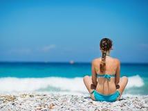 Femme s'asseyant sur la plage Photo stock