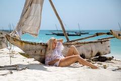 Femme s'asseyant sur la plage près du bateau Images stock