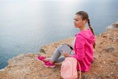 Femme s'asseyant sur la plage rocheuse au printemps Images stock