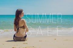 Femme s'asseyant sur la plage sablonneuse et les regards à la mer Photographie stock