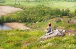 Femme s'asseyant sur la roche Images stock