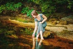Femme s'asseyant sur la roche dans un étang Photographie stock