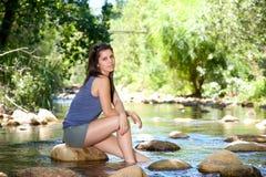 Femme s'asseyant sur la roche par un courant avec les pieds nus dans l'eau Photos stock