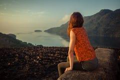 Femme s'asseyant sur la roche peu commune au lever de soleil Image stock