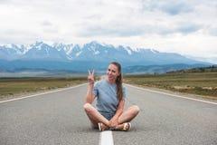 Femme s'asseyant sur la route images stock