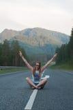 Femme s'asseyant sur la route Photo stock