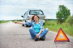 Femme s'asseyant sur la route près du signe de secours montrant des pouces  Images libres de droits