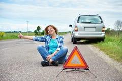 Femme s'asseyant sur la route près du signe de secours montrant des pouces  Photo stock