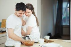 Femme s'asseyant sur la table, étreignant son mari photo libre de droits