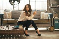 Femme s'asseyant sur la table basse en appartement de grenier image libre de droits