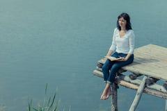 Femme s'asseyant sur la table de conseil près du lac Images libres de droits