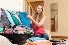 Femme s'asseyant sur la valise près ouverte de divan images stock