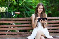 Femme s'asseyant sur le banc avec la tablette digitale Photos stock