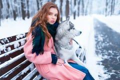 Femme s'asseyant sur le banc avec le chien de traîneau sibérien Photographie stock libre de droits
