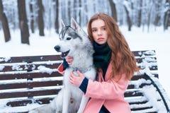 Femme s'asseyant sur le banc avec le chien de traîneau sibérien Image libre de droits