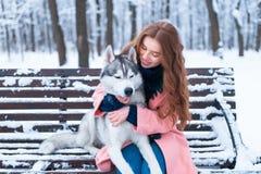 Femme s'asseyant sur le banc avec le chien de traîneau sibérien Photo libre de droits