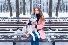 Femme s'asseyant sur le banc avec le chien de traîneau sibérien Photo stock