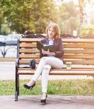 Femme s'asseyant sur le banc avec le journal intime Photos stock