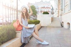 Femme s'asseyant sur le banc avec les livres et le sac à dos rouge Photos libres de droits