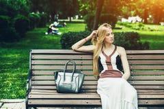 Femme s'asseyant sur le banc de stationnement Image libre de droits
