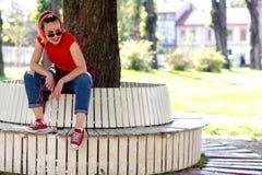 Femme s'asseyant sur le banc en parc et écoutant la musique d'a Image libre de droits