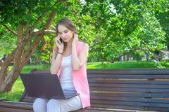 Femme s'asseyant sur le banc en parc parlant au téléphone portable et à l'aide de l'ordinateur portable photos stock
