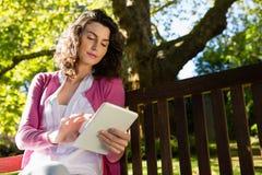 Femme s'asseyant sur le banc et à l'aide du comprimé numérique dans le jardin Image libre de droits