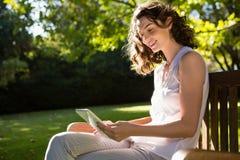 Femme s'asseyant sur le banc et à l'aide du comprimé numérique dans le jardin un jour ensoleillé Image stock